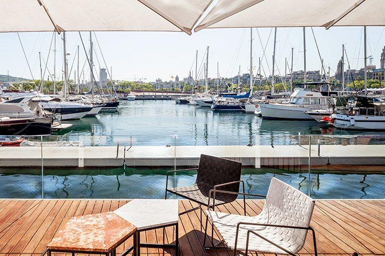 Loungestolar och bord på Blue Wave Cocktail Bars uteservering vid vattnet i Barcelona